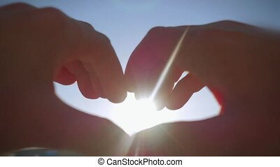 Female hands catch the sun in the sky and make a heart shape hands