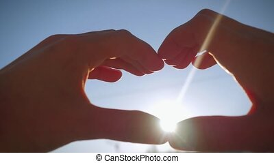 Female hands catch the sun in the sky and make a heart shape...