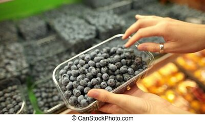 Female hands chooses the blueberry berry in a supermarket.