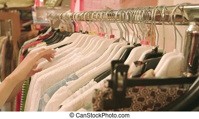 Female hands choosing clothes. Clothing on a rack.