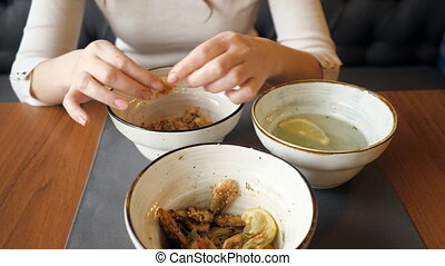 female hands cleans and eats shrimp in a restaurant, top...