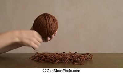 Female hands clewing the brown yarn
