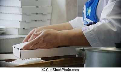 Female hands closing box for pizza in the kitchen