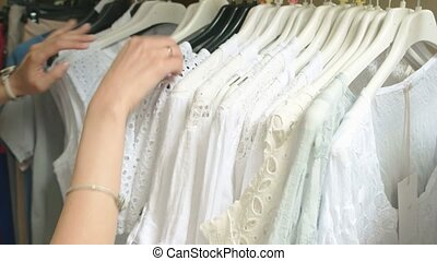 Female hands, clothes on rack.