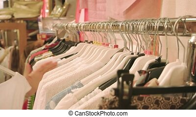 Female hands, clothing on rack. Clothes shop merchandise....