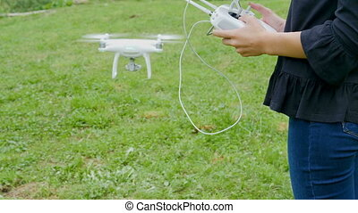 Female hands controlling drone with a transmitter remote...