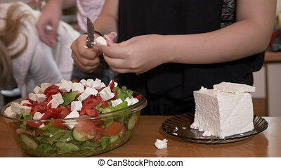 Female hands cook adding cheese to tasty healthy salad prepared in bowl while her friends gathering in the background in kitchen