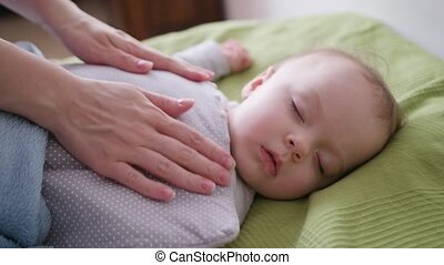 Female Hands Covering a Baby Lying in Bed
