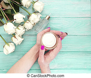 female hands, cream, flower rose on a blue wooden background
