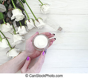 female hands, cream, flower rose on a   wooden background