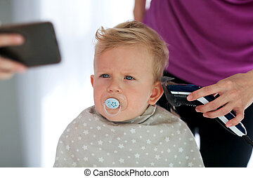 Female hands cut a child with a hair clipper in a hairdresser. A child watches cartoons on the phone and holds a dummy in his mouth. The first haircut.