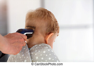 Female hands cut a child with a hair clipper in a hairdresser. The first haircut.