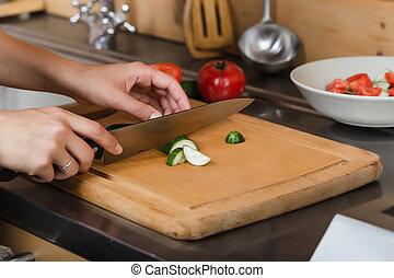 Female hands cut a cucumber on the board