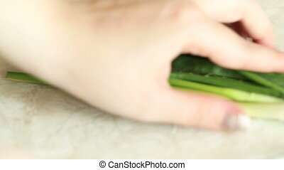 Female hands cut a green onion on small pieces.