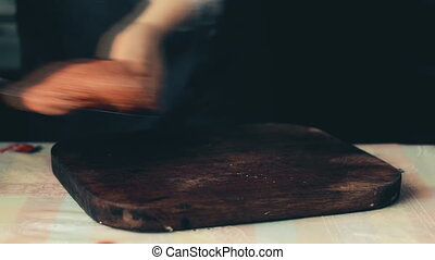 female hands cut salami on cutting board for cooking pizza on wooden background