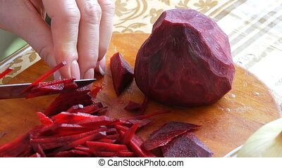 Female hands cut the beetroot on a kitchen board with knife