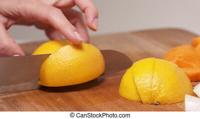 Female hands cuts orange into wedges on wooden chopping board closeup