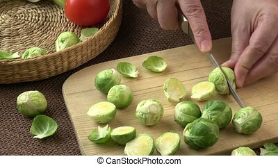 Female hands cutting Brussels sprouts on wooden board