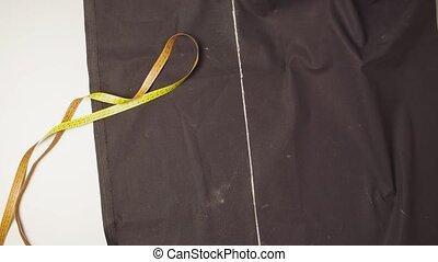 Female hands cutting cloth - Top view. Female hands cutting...