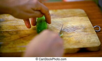 Female hands cutting cucumber on wooden board. Macro fast speed video