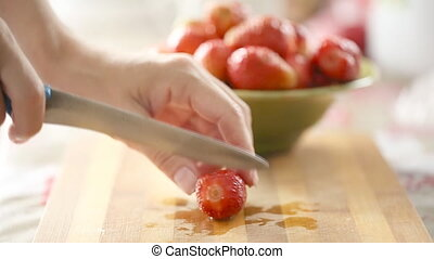 Female hands cutting fresh strawberry