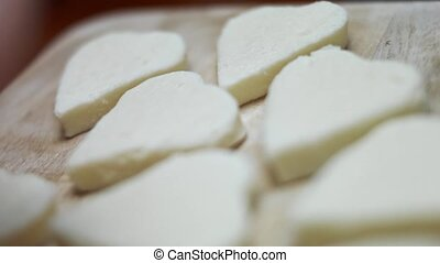 Female hands cutting heart shapes of mozzarella cheese on a wooden cutting board. Preparing food for Valentine's Day. 4k video. Artistic shooting