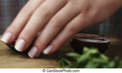 Female hands cutting red onion into rings at the table, on kitchen background.