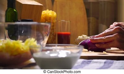 Female hands cutting red onion