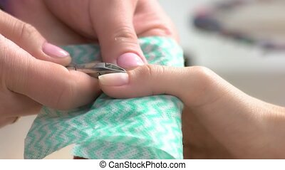 Female hands cutting the cuticle to woman. The process of...