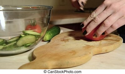 Female hands cutting tomato