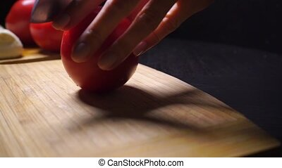Female hands cutting tomato on the wooden cutting board