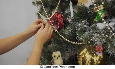 Female hands decorate artificial Christmas tree with bright...