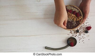 Female hands decorating acai smoothie bowl with berries raspberry and blueberry, granola and seeds.