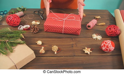 Female hands decorating gift red boxes for Christmas Holiday. Hands close up. Present packaging ideas.