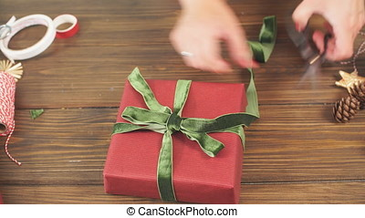 Female hands decorating gift red boxes for Christmas...
