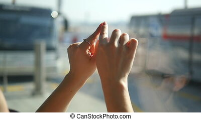 Female hands draw heart sign on window at airport. Arm of woman depict heart shape with sunny sky at background. Close up Slow motion