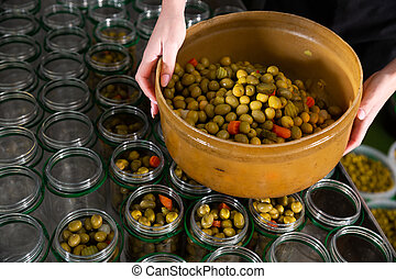 Female hands filling glass jars with pickled olives