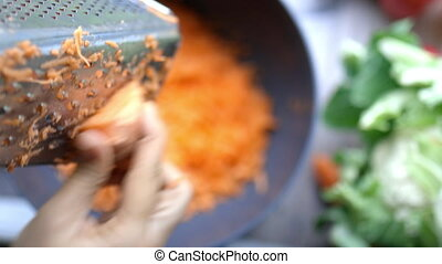 Female hands firmly grating carrot on metal grater and into bowl. Shredded carrots in bowl surrounded by vegetables. Vegan meal preparation
