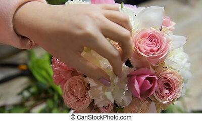 Arrange flowers in bouquet in flower shop