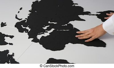 Female hands fixing a map of the world on a table
