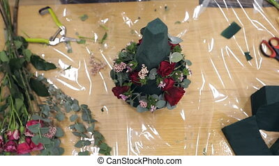 Female hands florist make a bouquet of roses, pine needles, leaves