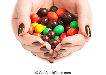 female hands full of colored candy