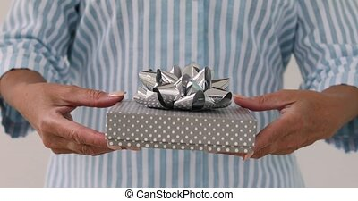 Female hands gives a gift in box with bow