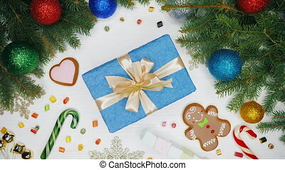 Female hands giving present wrapped in blue paper with...