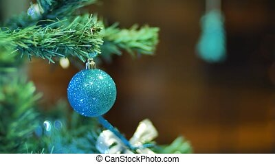 Female hands hanging balls on the Christmas tree. Winter holidays Christmas and New Year Decoration. Blinking Garland. Christmas Tree Lights Twinkling.