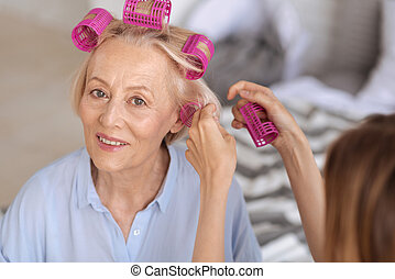 Female hands helping to put on hair rollers
