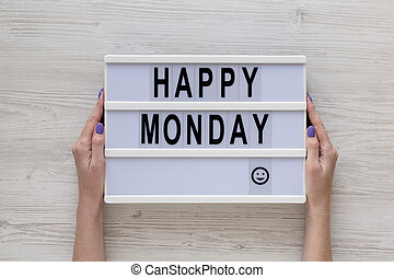 Female hands hold a lightbox with 'Happy monday' words over white wooden background, top view. Overhead, from above, flat lay. Close-up.