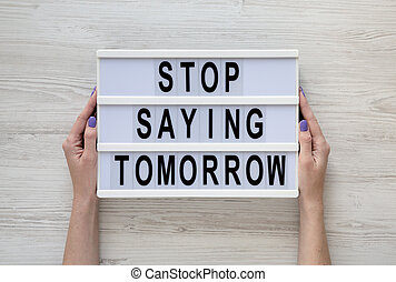 Female hands hold a lightbox with 'Stop saying tomorrow' words over white wooden background, top view. Overhead, from above, flat lay.