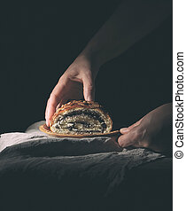 female hands hold baked roll with poppy seeds