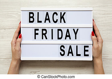 Female hands hold 'Black friday sale' word on lightbox over white wooden background, top view. From above, overhead.
